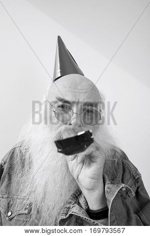 Portrait of senior man wearing party hat and red glasses while blowing horn against gray background
