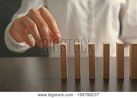 Businesswoman hand trying to toppling dominoes on table