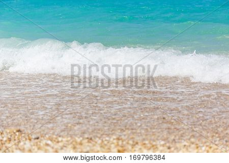 White waves on the beach with blue sea