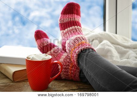 Human legs in knitted socks on windowsill beside cup of coffee and books