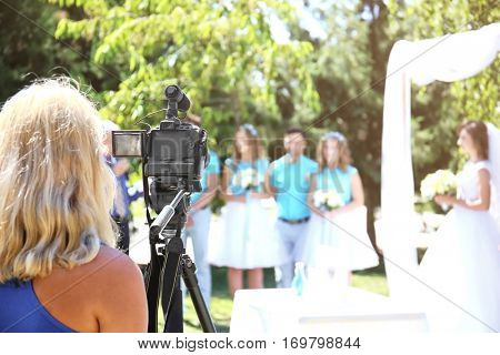 Camerawoman recording video and newlyweds on background