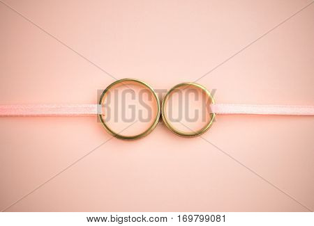 Stylish Wedding or Engagement background - pair of golden wedding rings and gentle pink ribbons and backdrop, copy space for text