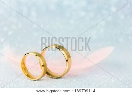 Sparkling Wedding Card - Two Golden Wedding Rings and Light Angelic Feather - gentle soft background for marriage