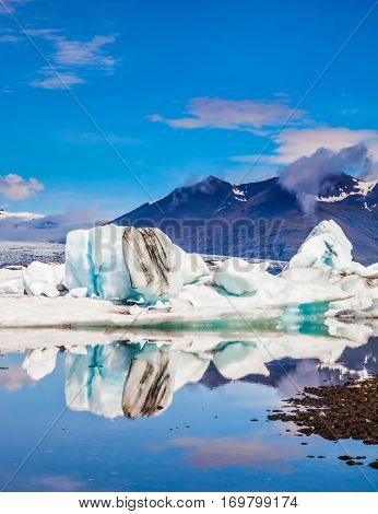 Icebergs and ice floes are reflected in the smooth water surface. Morning in the Ice Lagoon. Drift ice Ice Lagoon - Jokulsarlon. The concept of extreme northern tourism