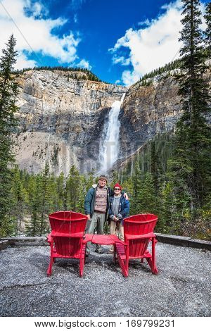 Pair of elderly tourists  are photographed in front of the famous waterfall. Two red deck chairs to relax in front of the waterfall Takakkaw. Autumn in Yoho National Park in the Rocky Mountains