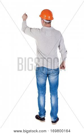 back view of writing engineer in construction helmet. Young gay in jeans draws. Rear view people collection.  backside view of person. Isolated over white background.