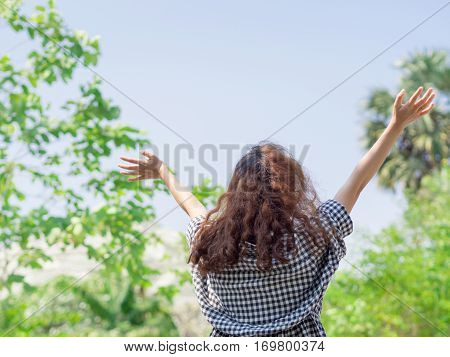 Indie girl so happy raise hands up to the sky with blurred background