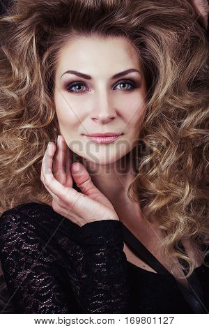 Model with blonde long hair in guipure clothing. Waves Curls Hairstyle. Fashion model with shiny hair. Woman with healthy hair. Girl with luxurious haircut and hair volume.