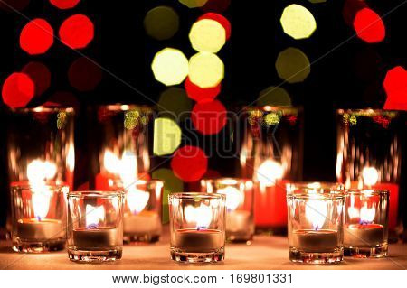 A small lighting lamps with red color aromatic paraffin in a small glasses with a blur big red candles in the big glass in the back and enneagon bokeh blur light of light bulb in the background
