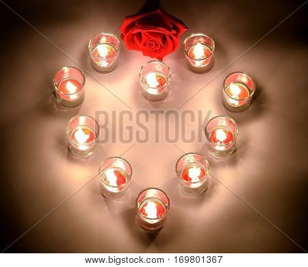 A small lighting lamps with red color aromatic paraffin in a small glasses arrange in heart form with a red rose symbol of love and valentine's day on a top of the heart put on a white floor in the night
