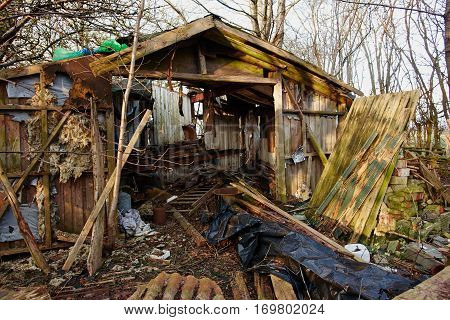 Old abandoned dirty wooden shed in a forest