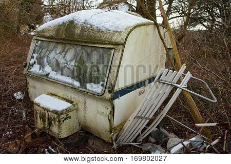 Old Vintage Dirty Abandoned Camper Camping Wagon Caravan in a small forest