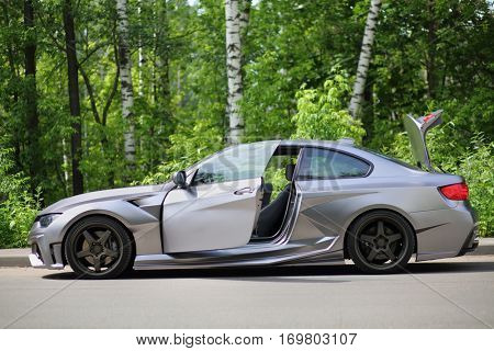 MOSCOW - JUN 19, 2016: Silver sportscar with an open door on road in front of green foliage