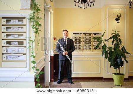 Handsome man in a business suit and tie standing with a silver umbrella in the hallway near the entrance
