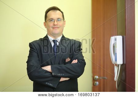 Smiling concierge stands with his arms crossed behind the counter at his workplace near the telephone