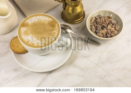 A cup of coffee with milk with a butter cookie and a milk jar on a white marble table, with a place for text