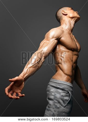 Bodybuilders hand and arm with veins protruding from under the thin skin. isolated on black background with clipping path