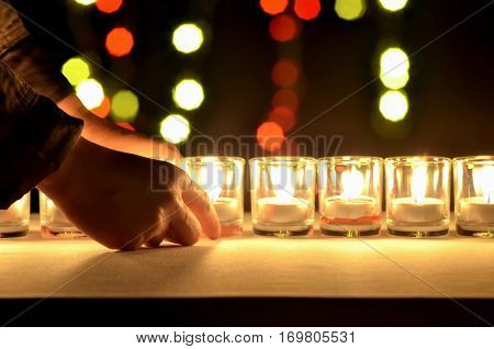A small glasses that contain a small lamp are arranging in a row by a hands of a woman with a enneagon red and yellow bokeh form a blur light blub in the background