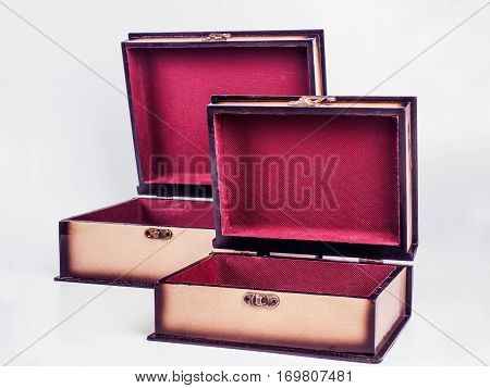 Picture of two opened wooden jewel-box with red fit-out on white background. Handmade boxes for bijouterie. Side view.