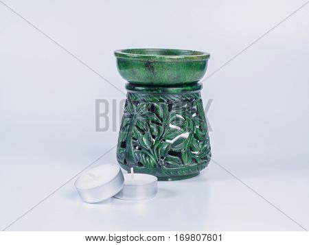 Picture of a green aroma lamp with two candles made of stone isolated on white background. Made of stone aroma lamp with floral ornaments.