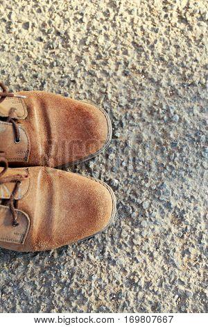 Feet in shoes on asphalt background