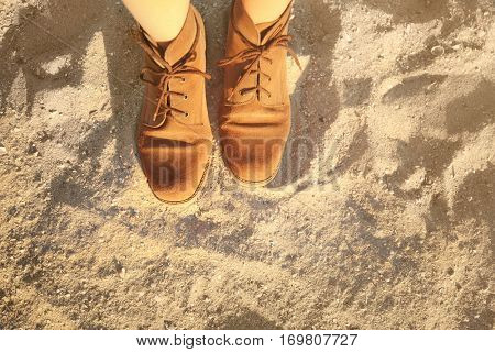 Feet in shoes on sand background