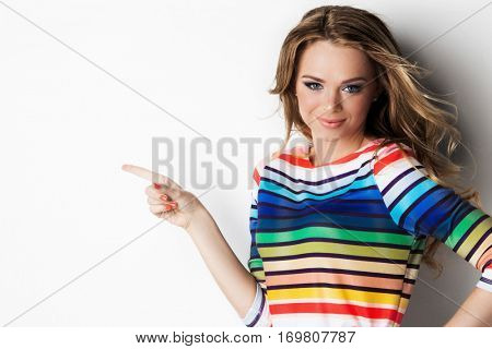 Pretty cheerful young woman pointing with finger to empty copy space