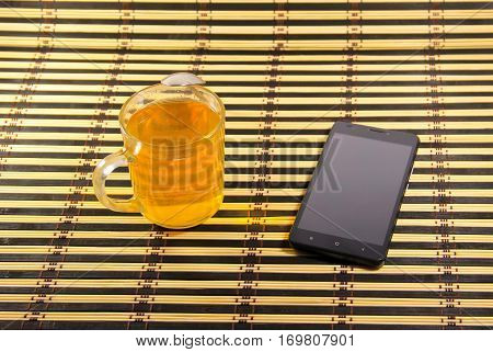 Black smartphone and cup of tea on the bamboo mat