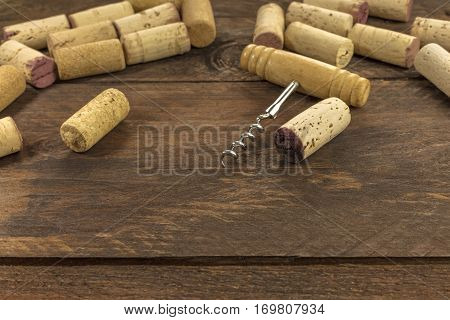 A photo of an old-fashioned corkscrew with corks on a dark wooden background texture with plenty of copy space. A design template for a wine list or a tasting invitation