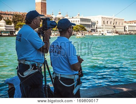 VENICE ITALY - AUGUST 17 2016: Police officers watch tourists through special optical equipment on August 17 2016 in Venice Italy.