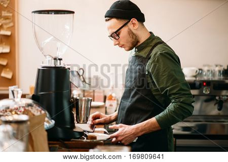 Barman making check in cafe