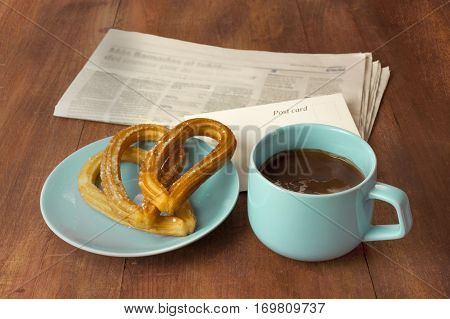 Plate of churros, traditional Spanish, especially Madrid, dessert, particularly for Sunday breakfast, with cup of hot chocolate, blurred newspaper, and blank postcard