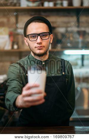 Barman in black apron stretches plastic cup