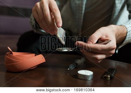 Narcotic dependence man preparing a dose of heroin