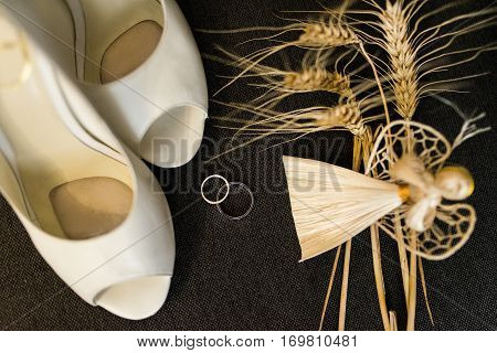 Wedding decoration details. Silver wedding rings and elegant bridal shoes on a grey background and handmade angel of straw
