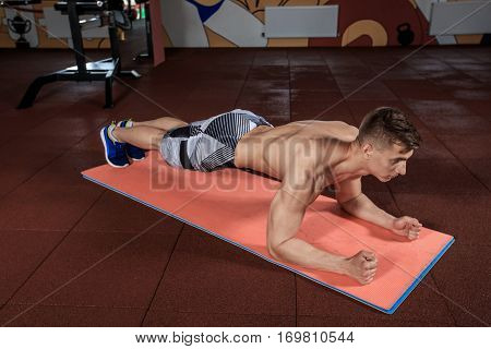 Confident muscled young man wearing sport wear and doing plank position while exercising on the floor at the gym. Plank it