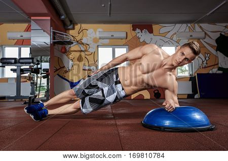 Portrait of a muscular man doing bosu ball exercises at crossfit gym.