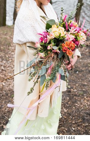 Wedding details. Closeup of female hands holding bridal rustic bouquet with yellow, pink, orange flowers, greenery with long ribbon