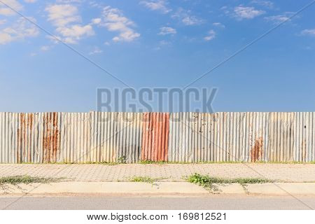 galvanized sheet fence and footpath beside asphaltic road with blue sky background
