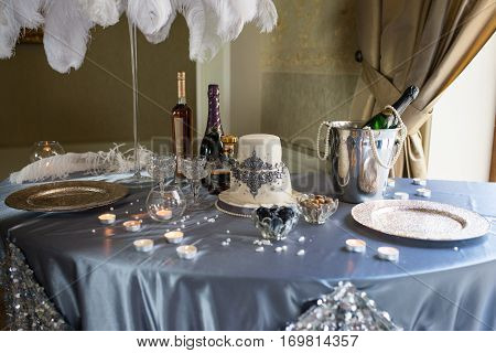 Wedding banquet table decorated with two tier white wedding cake, stemware, bottles of cognac and champagne, candles, nuts, ice bucket, silver tray and ostrich feathers on a grey tablecloth
