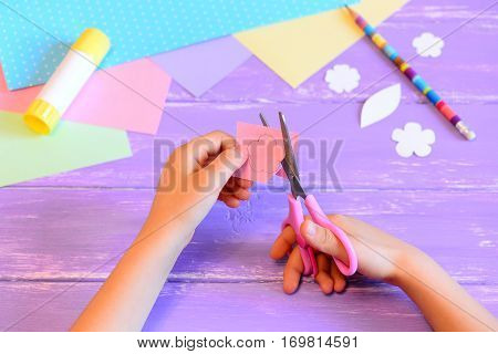 Small child makes a greeting card for mom. Child holds scissors and cuts a flower from paper. Materials and tools for art crafts on a wooden table. Mother's day or March 8 paper crafts idea