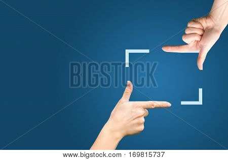 Female Hands Showing Cropping Composition Gesture. Isolated On Blue.