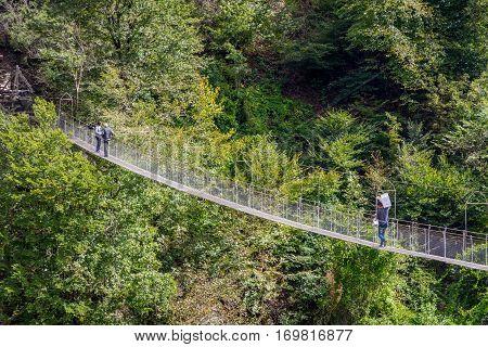 People Passing Over The Hanging Monkey Bridge