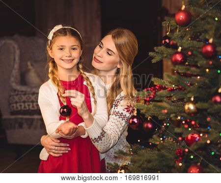Smiling mother and daughter decorating christmas tree