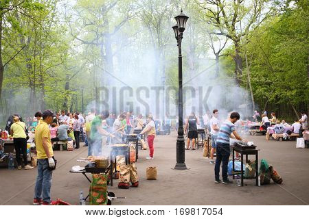 MOSCOW - MAY 08, 2016: Vacationers people make shashlik in the barbecue area in Ostankino park