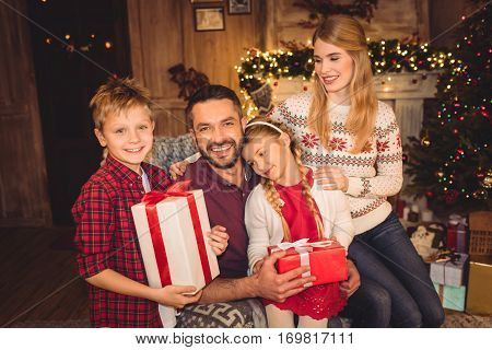 Happy family holding gift boxes at christmastime