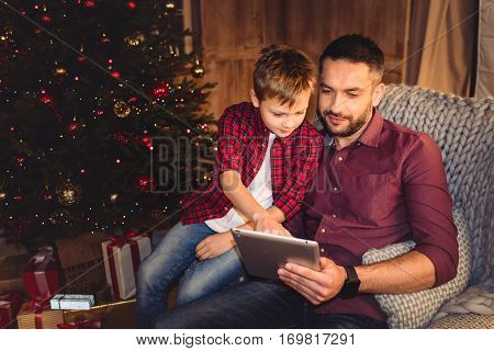 Little son with happy father near christmass tree at home