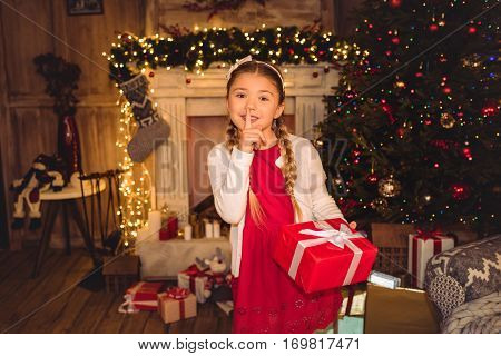 Girl holding christmas present and gesturing for silence