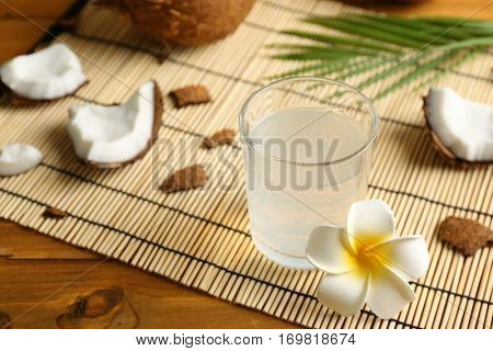 Glass of coconut water and beautiful plumeria flower on straw mat