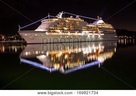 Large luxury cruise ship on sea water at night with illuminated light docked at port of st.Johns Antigua